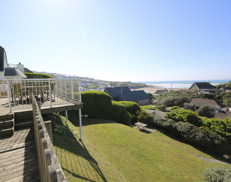 The wooden deck overlooking the garden of Balderstone, a holiday house in Polzeath, Cornwall, with seaviews.