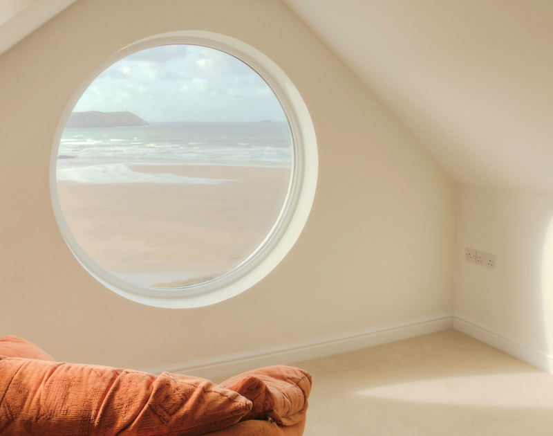 The porthole window in the playroom on the top floor at Treverden, a family holiday house to rent in New Polzeath, Cornwall.