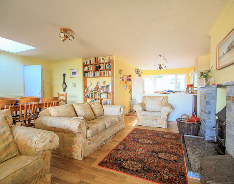 The open-plan sitting room of Stradav, a holiday house in Polzeath, Cornwall, with its woodburner.