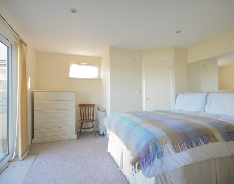 The master bedroom with sliding glass doors at Dozmary, a self catering holiday house by the sea in Polzeath, Cornwall.