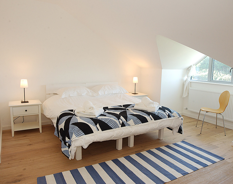 A stylish double bedroom at Rock Pipit, a holiday rental in Polzeath, Cornwall, with 6ft zip and link beds.