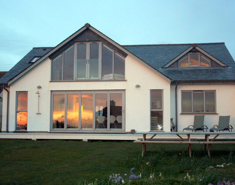 Sunset reflected in the windows of Rock Pipit, a stunning self-catering holiday house in Polzeath, North Cornwall and lawned garden.