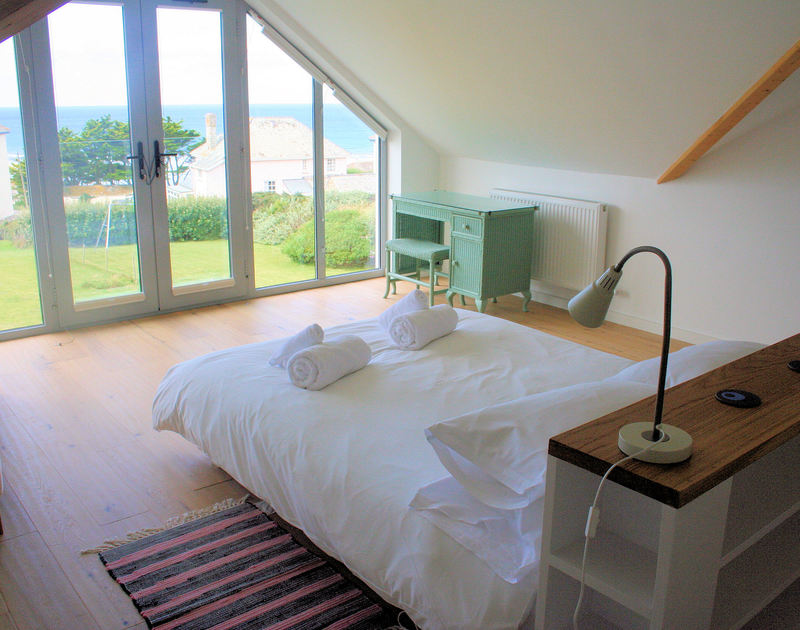 The master bedroom of Rock Pipit, a stunning holiday house at Polzeath, Cornwall, with balcony doors and seaviews.