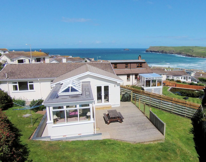 An aerial view of the bay and Atlantis, a seaside holiday house to rent with a garden at Polzeath in North Cornwall.