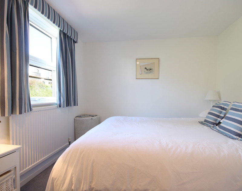 The first floor double bedroom at One Slipway Cottage, a waterside holiday rental in Rock, Cornwall, with kingsize bed.
