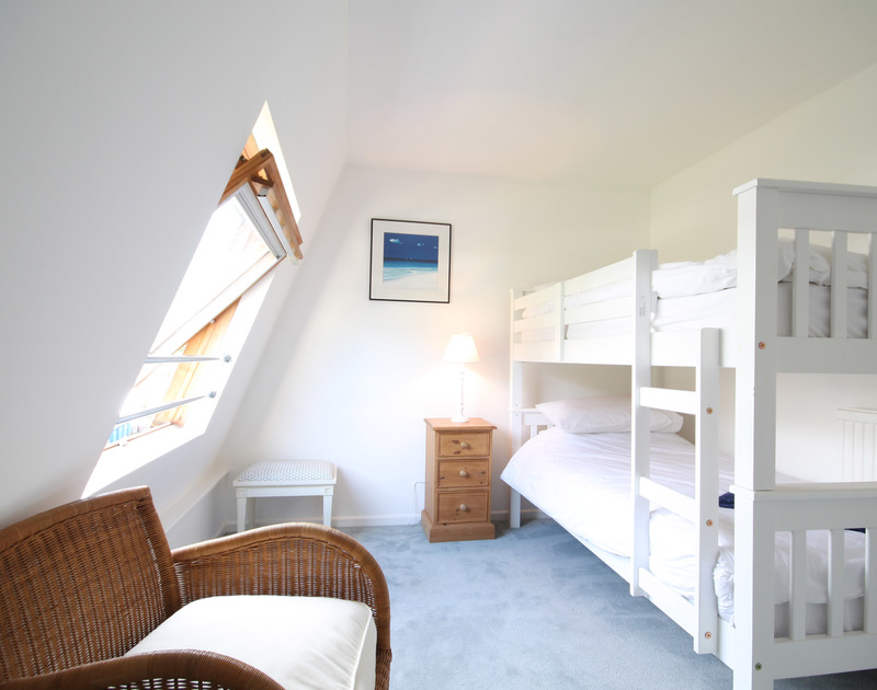 Attractive bunkroom at One Slipway Cottage, a waterside holiday rental in Rock, Cornwall, with its velux window.