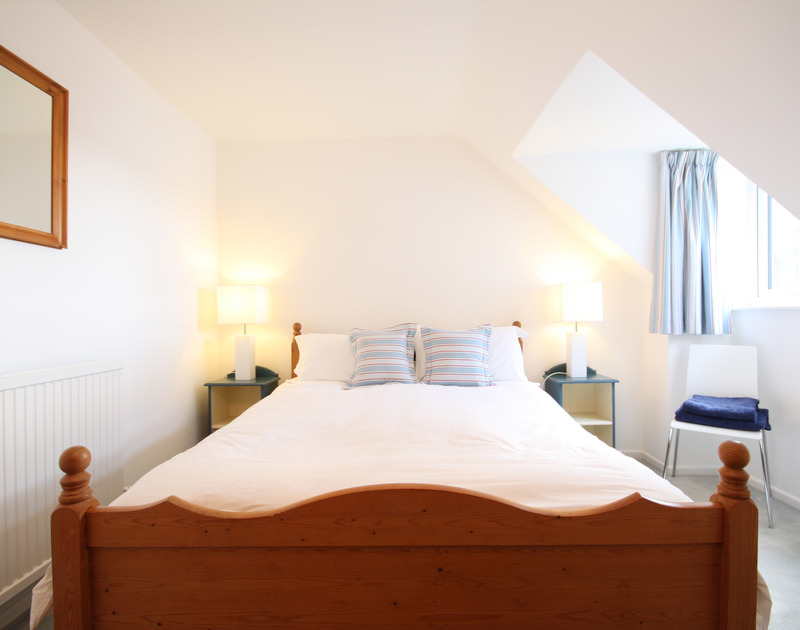 A cosy double bedroom at One Slipway Cottage, a waterside holiday rental in Rock, Cornwall