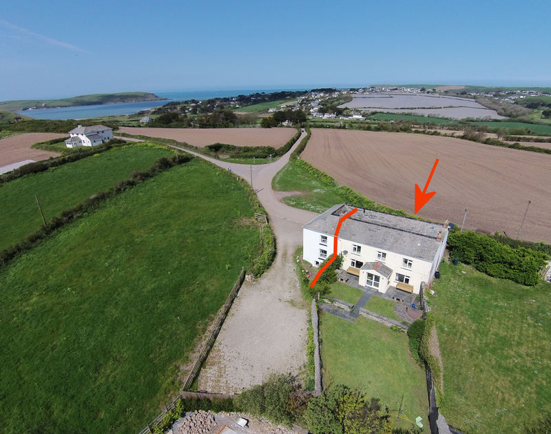 A heli shot of semi-detached, self catering, family, holiday rental Trewint Farmhouse, close to the mouth of the Camel estuary at Daymer Bay in North Cornwall.