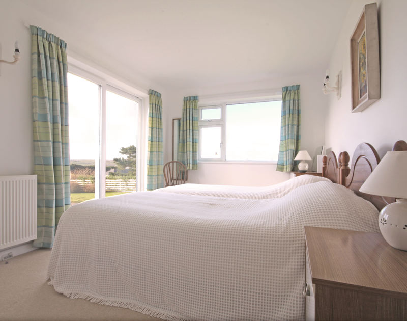 A ground-floor twin bedroom at Broadagogue, a holiday house at Daymer Bay, Cornwall, with doors to the garden.