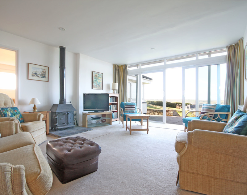 The spacious sitting room at Broadagogue, a coastal holiday house at Daymer Bay, Cornwall, with sliding doors to the terrace.