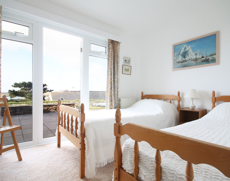 One of three ground-floor twin bedrooms at Broadagogue, a holiday house near Daymer Bay, Cornwall, with door to the garden.