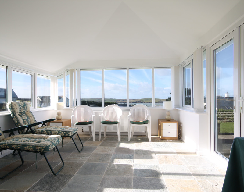 The sunroom at Broadagogue, a coastal holiday house near Daymer Bay, Cornwall, with sun loungers and doors to the terrace.