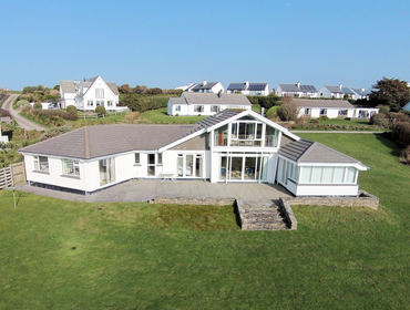 An aerial view of Broadagogue, a coastal holiday house at Daymer Bay, Cornwall, with its large lawned garden.