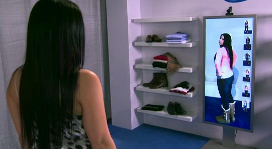 Девушка примеряет одежду перед «умным» зеркалом, позволяющим оценить другие расцветки наряда, получить обзор на 360 градусов и узнать доступность размеров