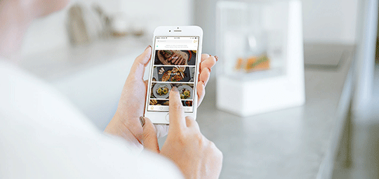 Woman using smartphone app for cooker