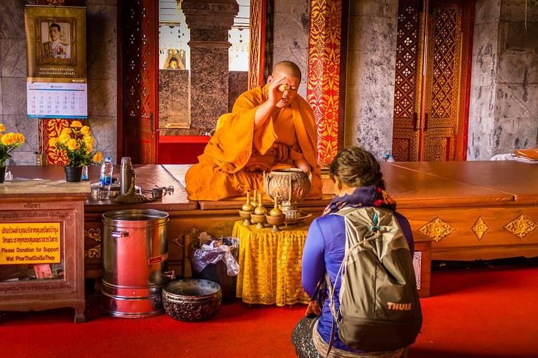Een monnik in Wat Phrathat Doi Suthep in Chiang Mai