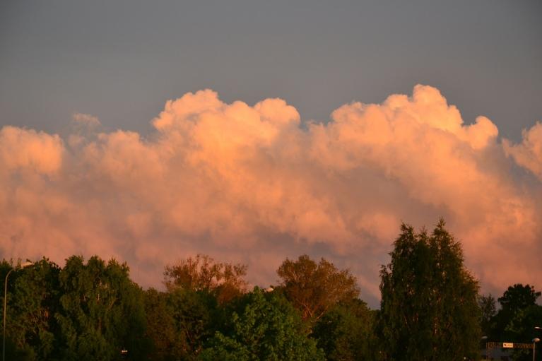 23. maijā Rīgā rietošā saule dienvidaustrumu pamalē nokrāso gubumākoņus.