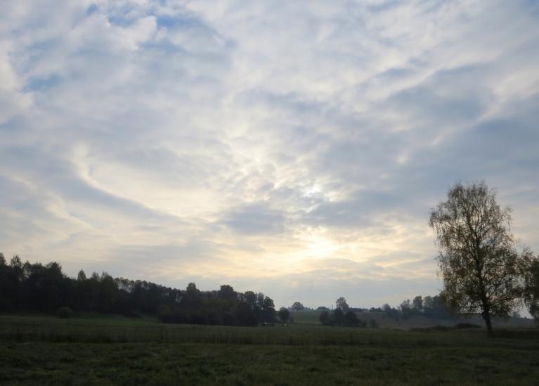 Rīta pusē saule slēpjas aiz dūmakainiem mākoņiem.