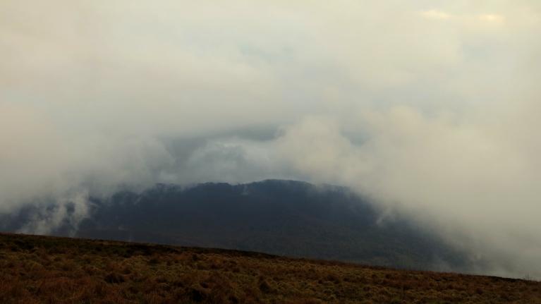 """Kalna galā ir milzu migla (mākonis), bet lejup kāpjot uz mirkli paveras """"debesu vārti"""" ļaujot saskatīt  kaut ko nedauzd no pretējo kalnu panorāmas."""""""