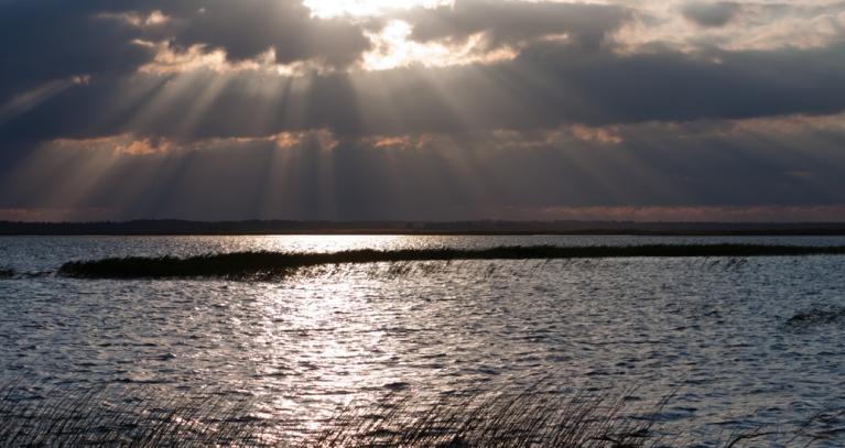 Saules stari starp mākoņiem Engures ezerā.