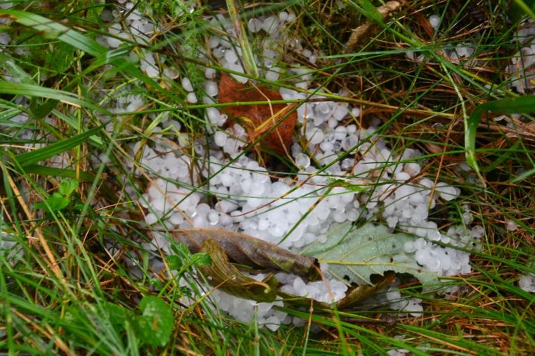 Tikai pie Slutišku sādžas izdodas novērtēt tikko pāri pārgājušā negaisa sekas - zemē mētājas krusas graudi, ceļš daļēji izskalots un saputots.