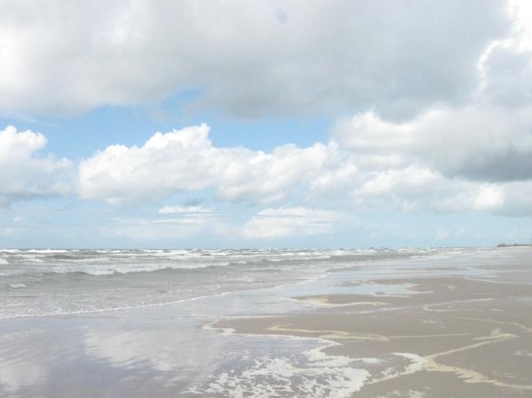 Vilnis saplūst ar pludmales smilktīm un Saules gaismas spēli.
