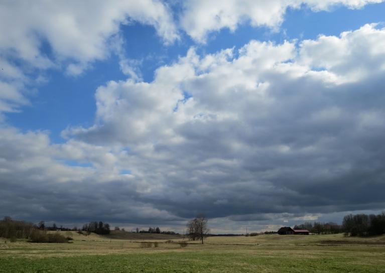 Pēcpusdienā saule sasilda zemi, draudīgi mākoņi gan turpina apkārt staigāt.