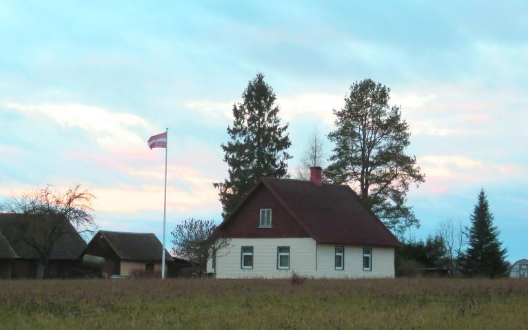 Vējš cītīgi plivina pie mājām izkārtos karogus.
