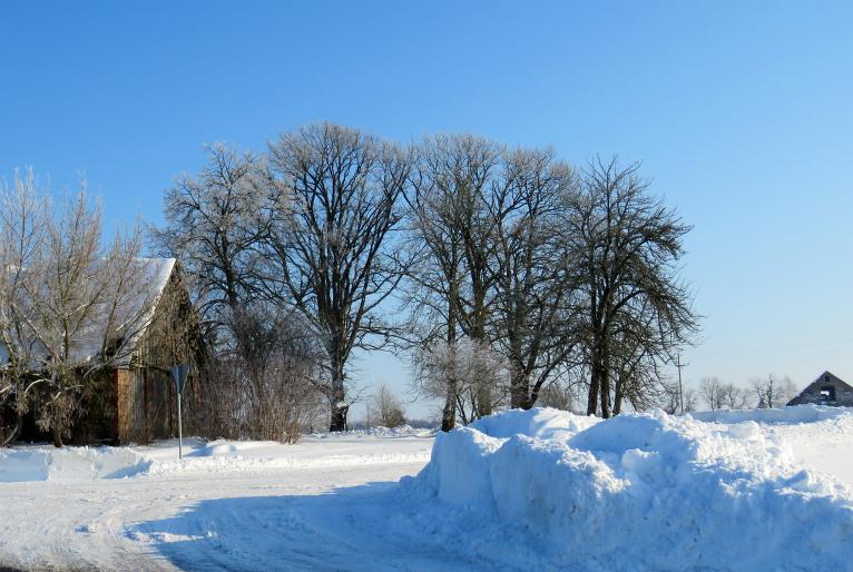 Ceļu līkumos sastumti sniega kalni.