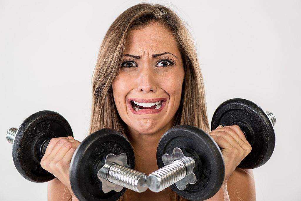 Stressed girl ready to use dumbbell set