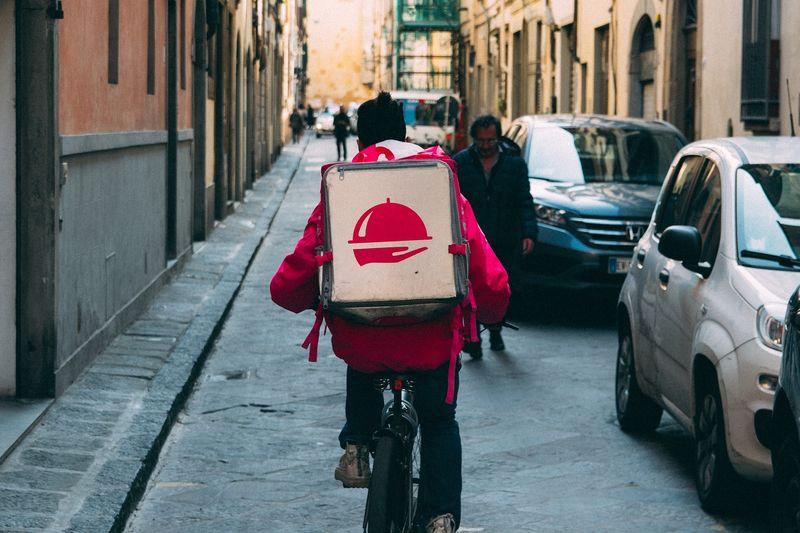 uomo in bici che consegna a domicilio