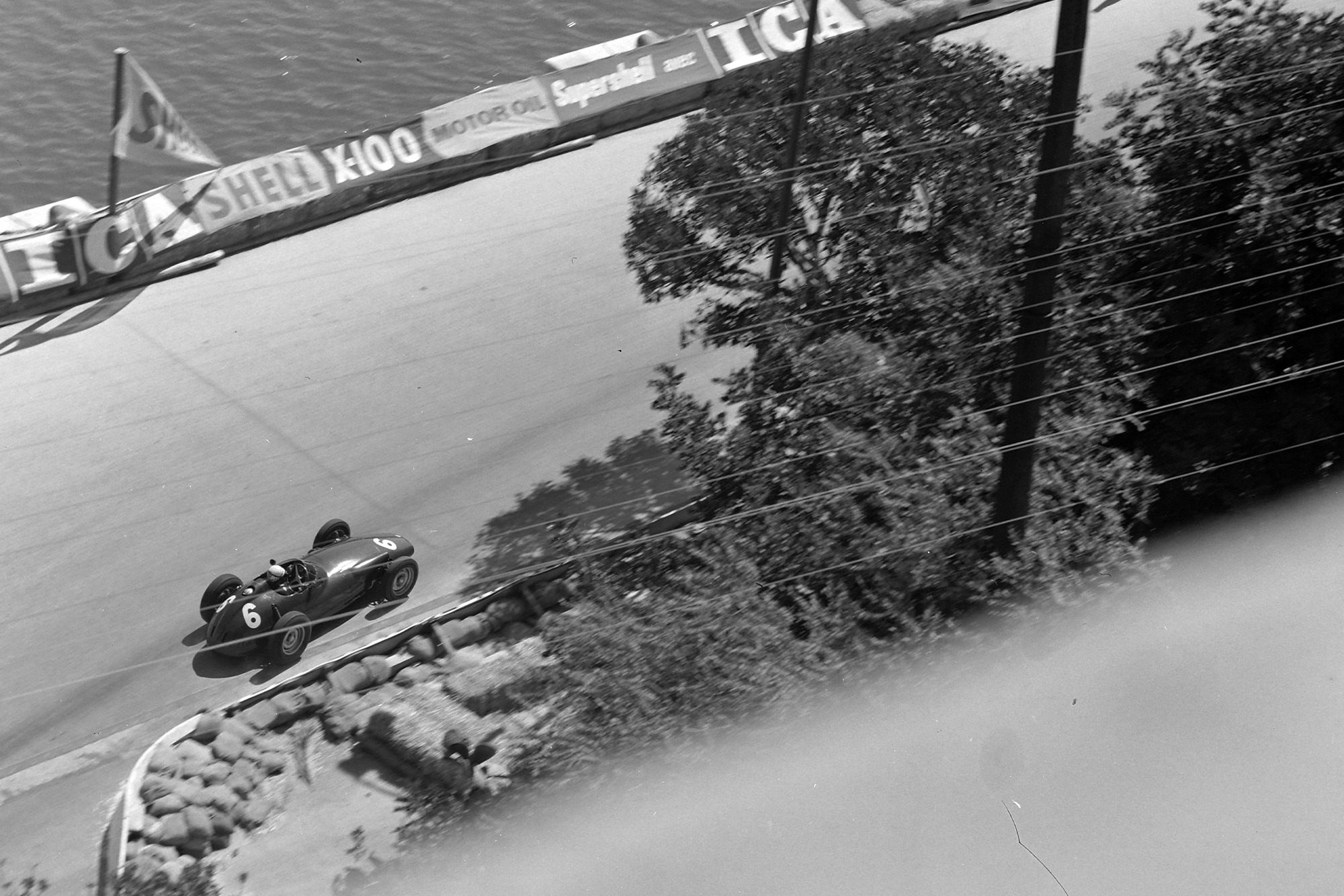 Jean Behra drives past the harbour in his BRM.