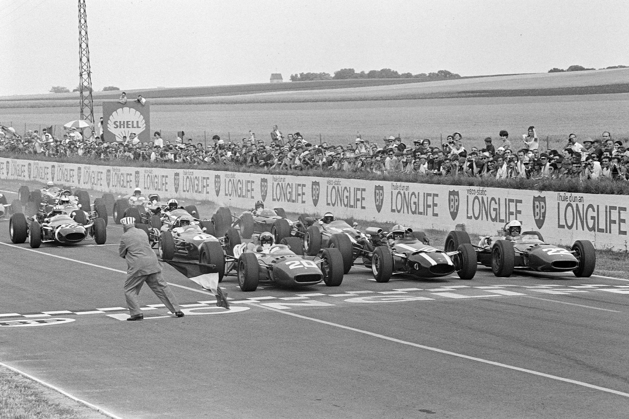 The race begins as the French Tricolore is waved, with Lorenzo Bandini, Ferrari 312, John Surtees, Cooper T81 Maserati and Mike Parkes, Ferrari 312 on the front row.