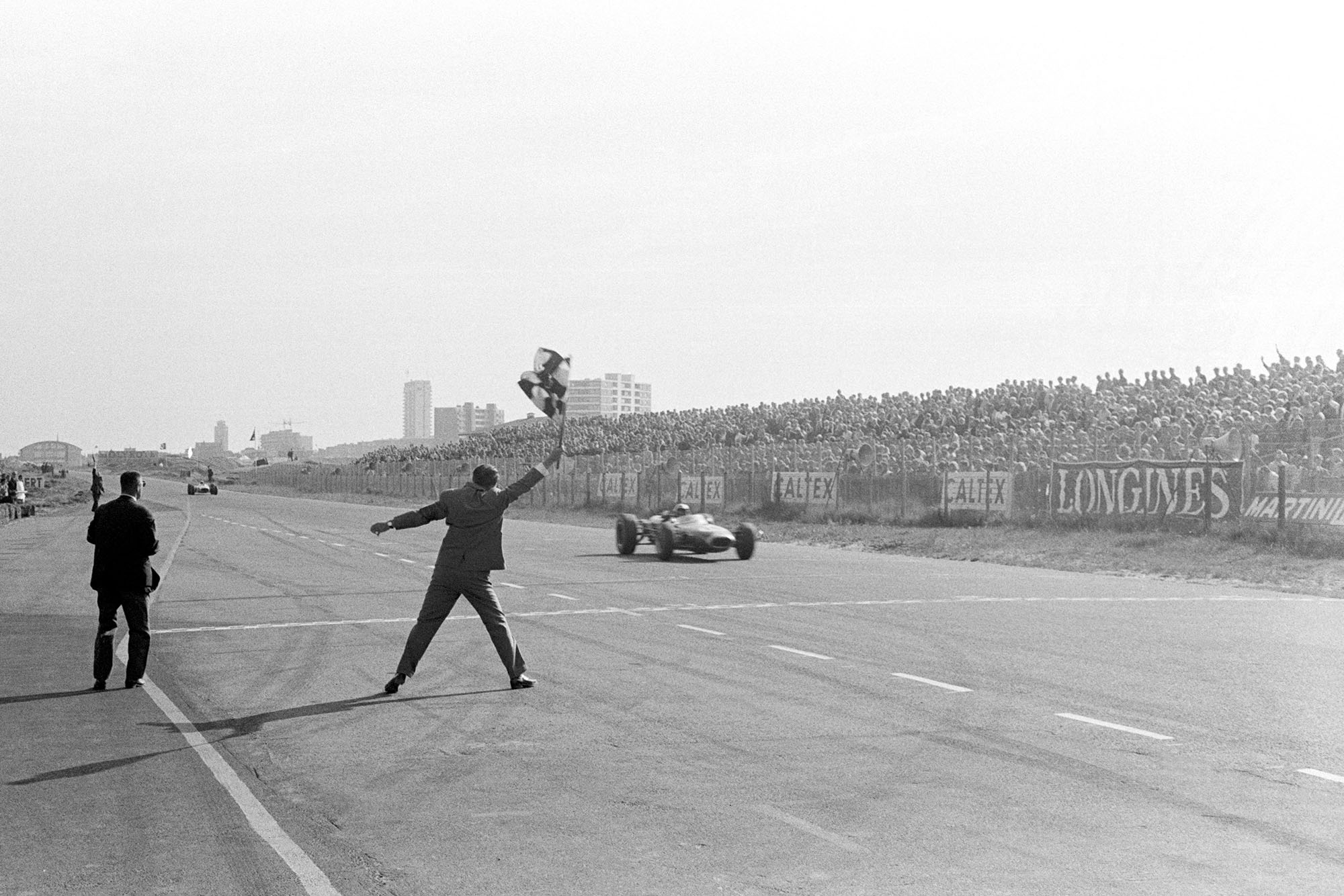 Race winner Jack Brabham (AUS) Brabham BT19 takes the chequered flag to score his hat-trick of consecutive victories.