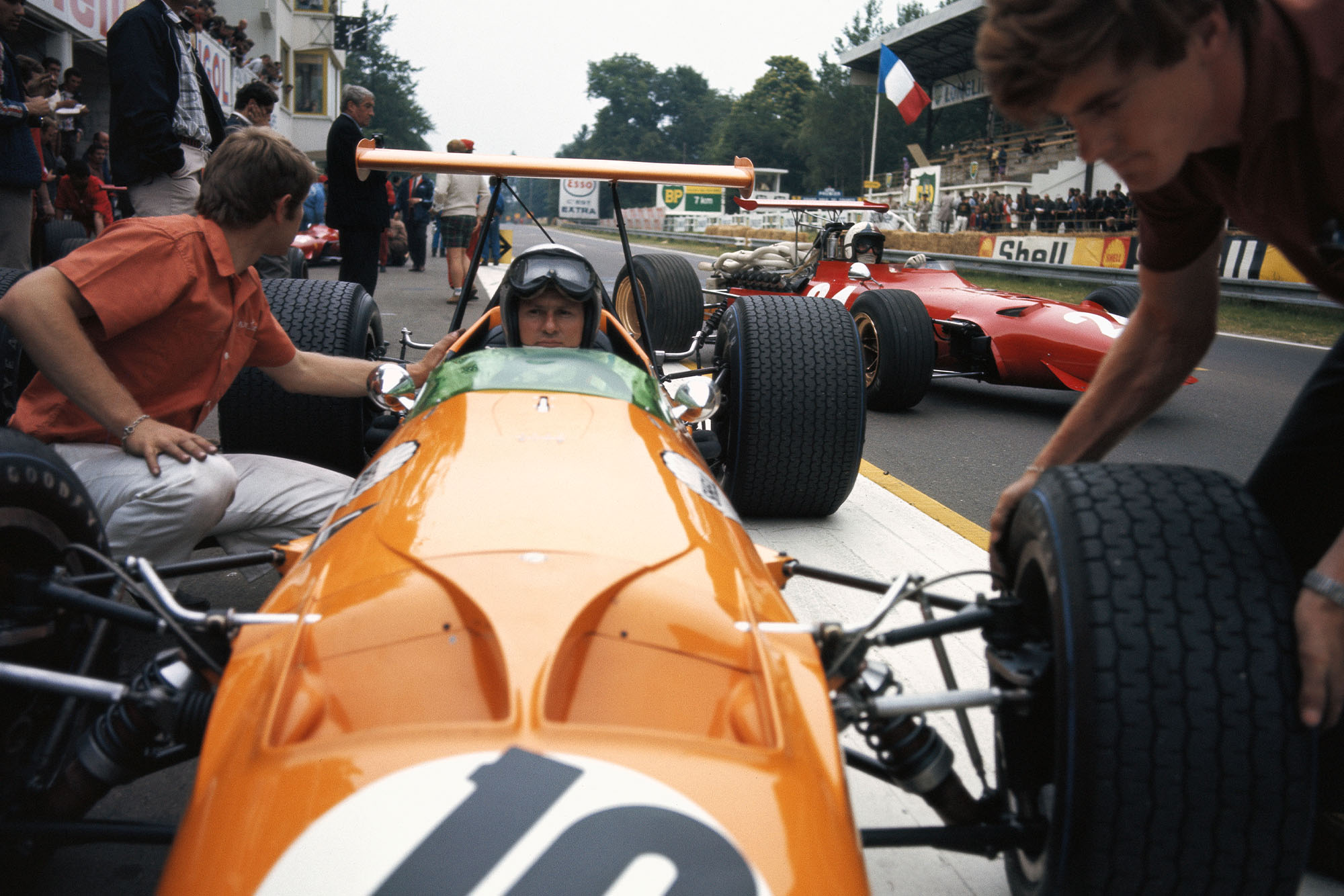 Bruce McLaren, McLaren M7A Ford, getting new tyres while Chris Amon, Ferrari 312, leaves the pits.