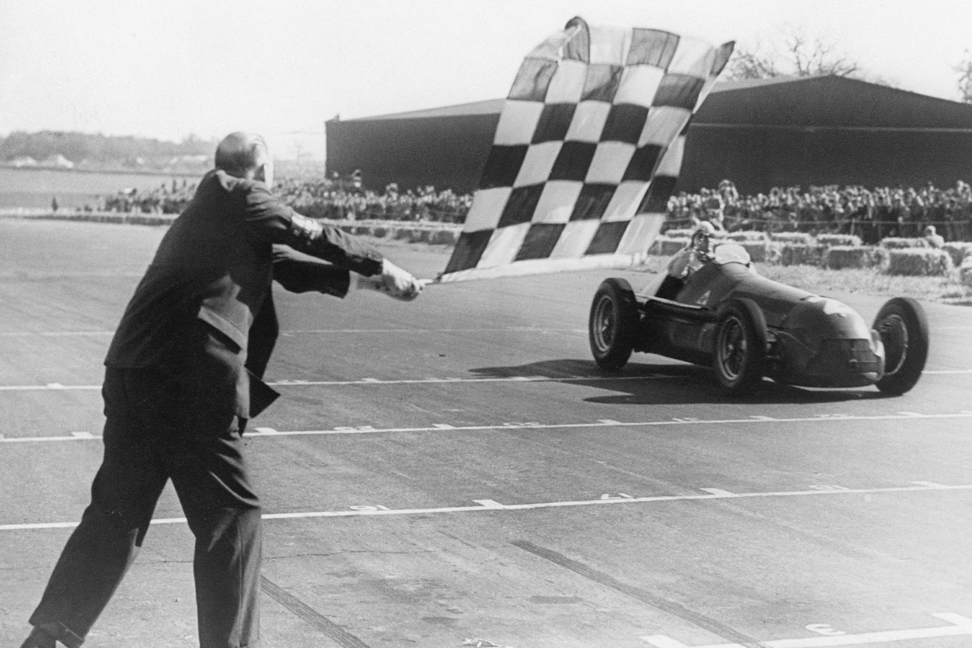 Giuseppe Farina takes the chequered flag to win the 1950 British Grand Prix at Silverstone