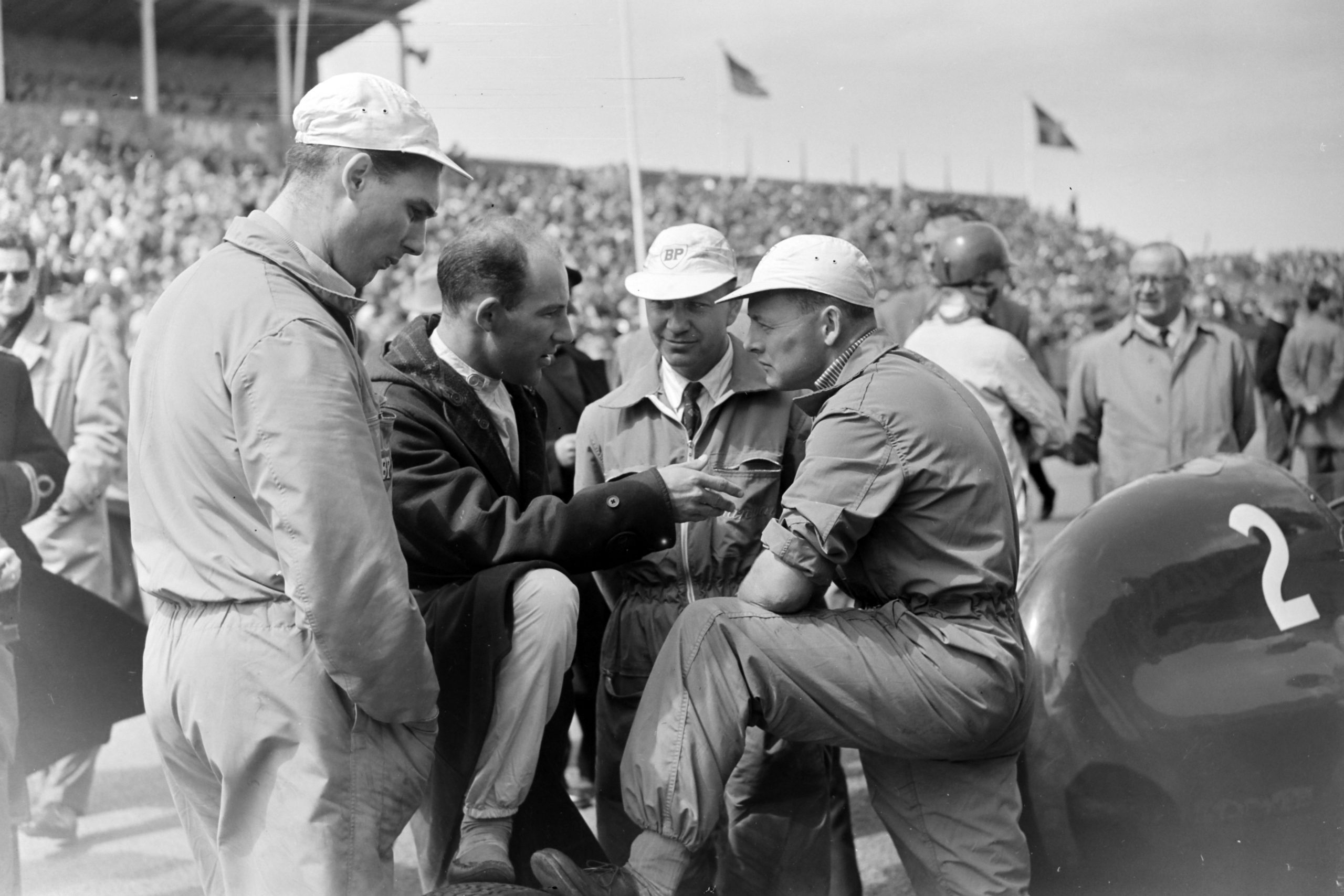 Stirling Moss speaks with mechanics before the race