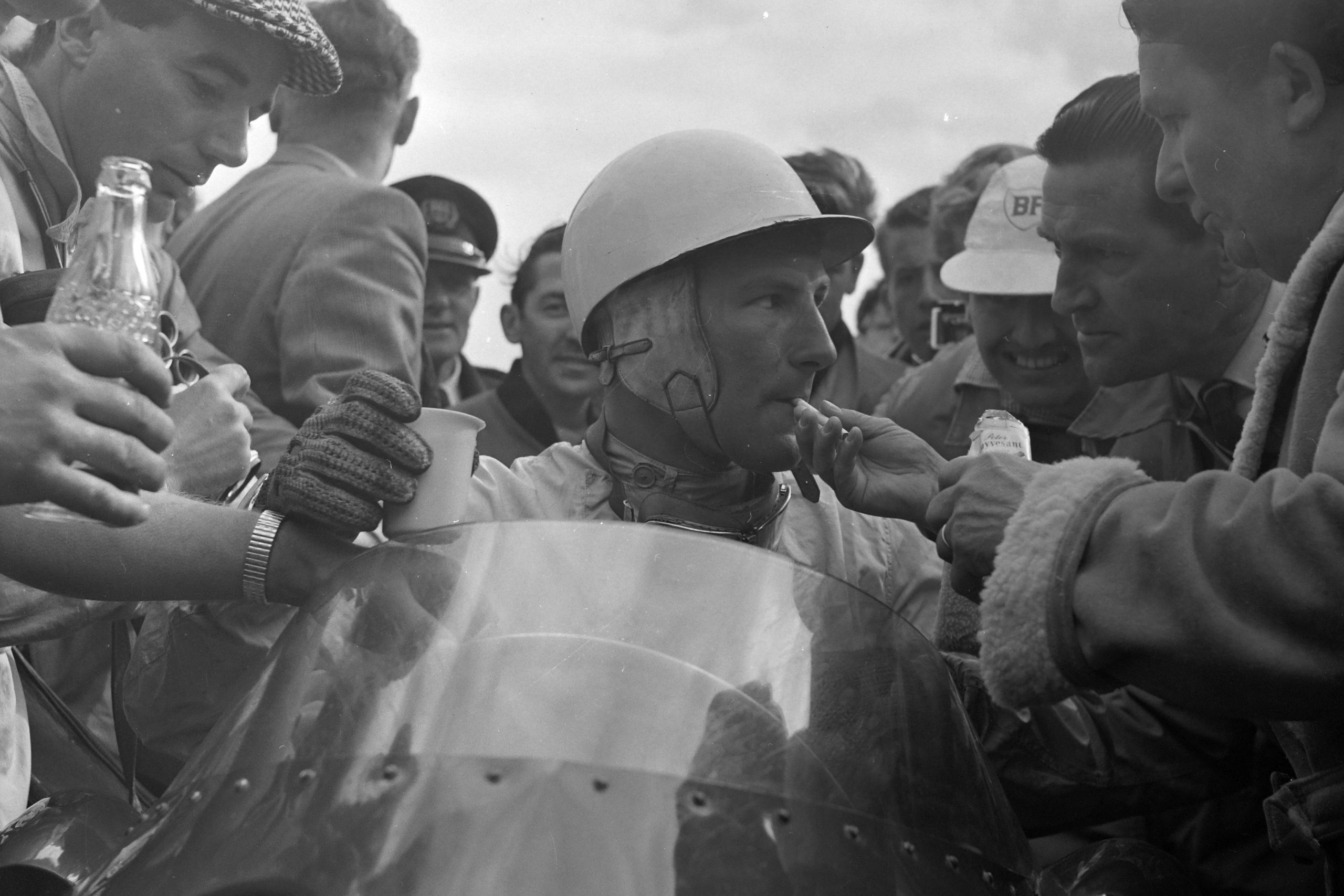 Stirling Moss is handed a cigarette and a drink following his victory.