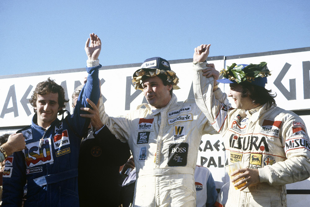 Winner Alan Jones celebrates on the podium with second placed Alain Prost and third placed Bruno Giacomelli.