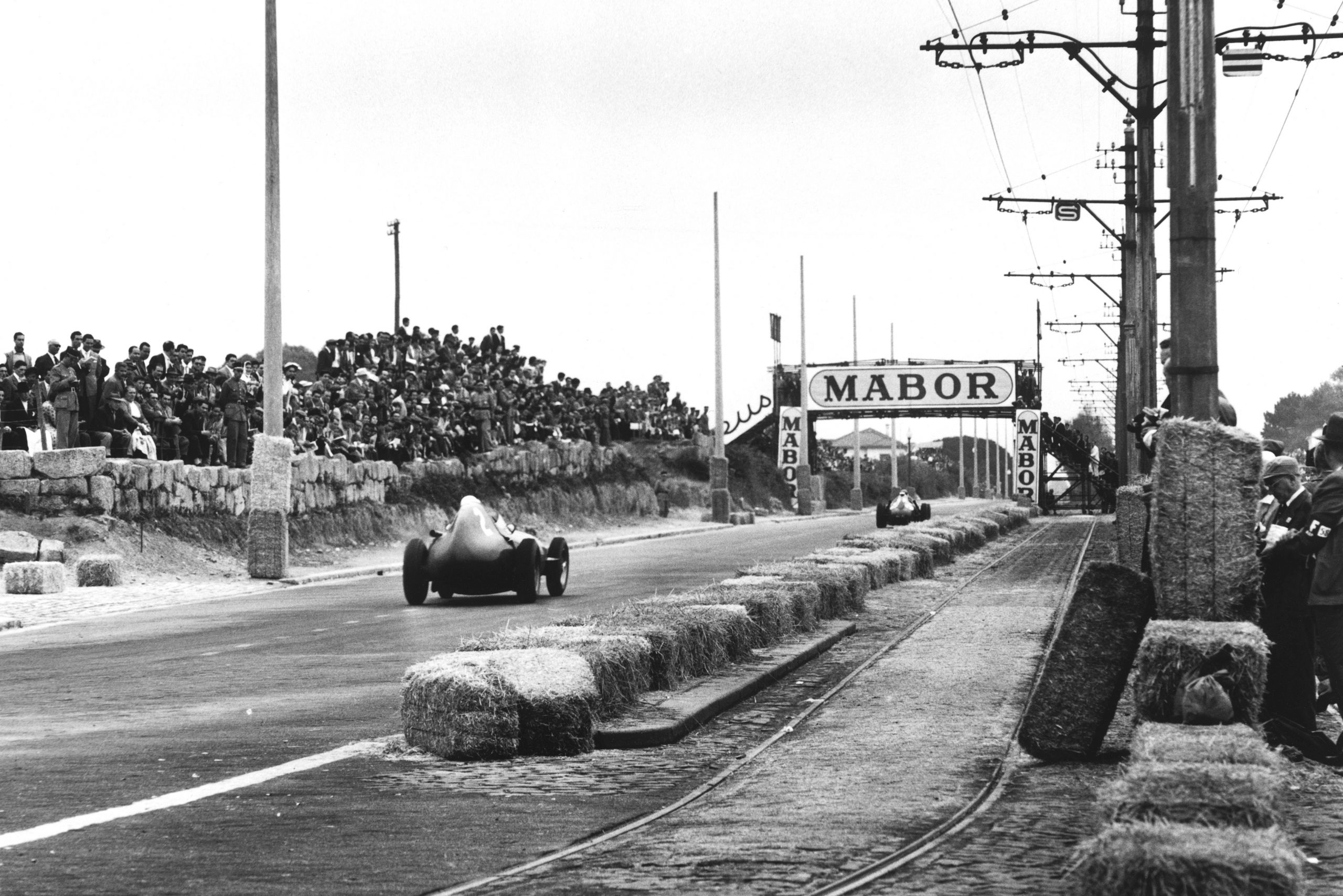 Stirling Moss driving a Vanwall) to 1st place.