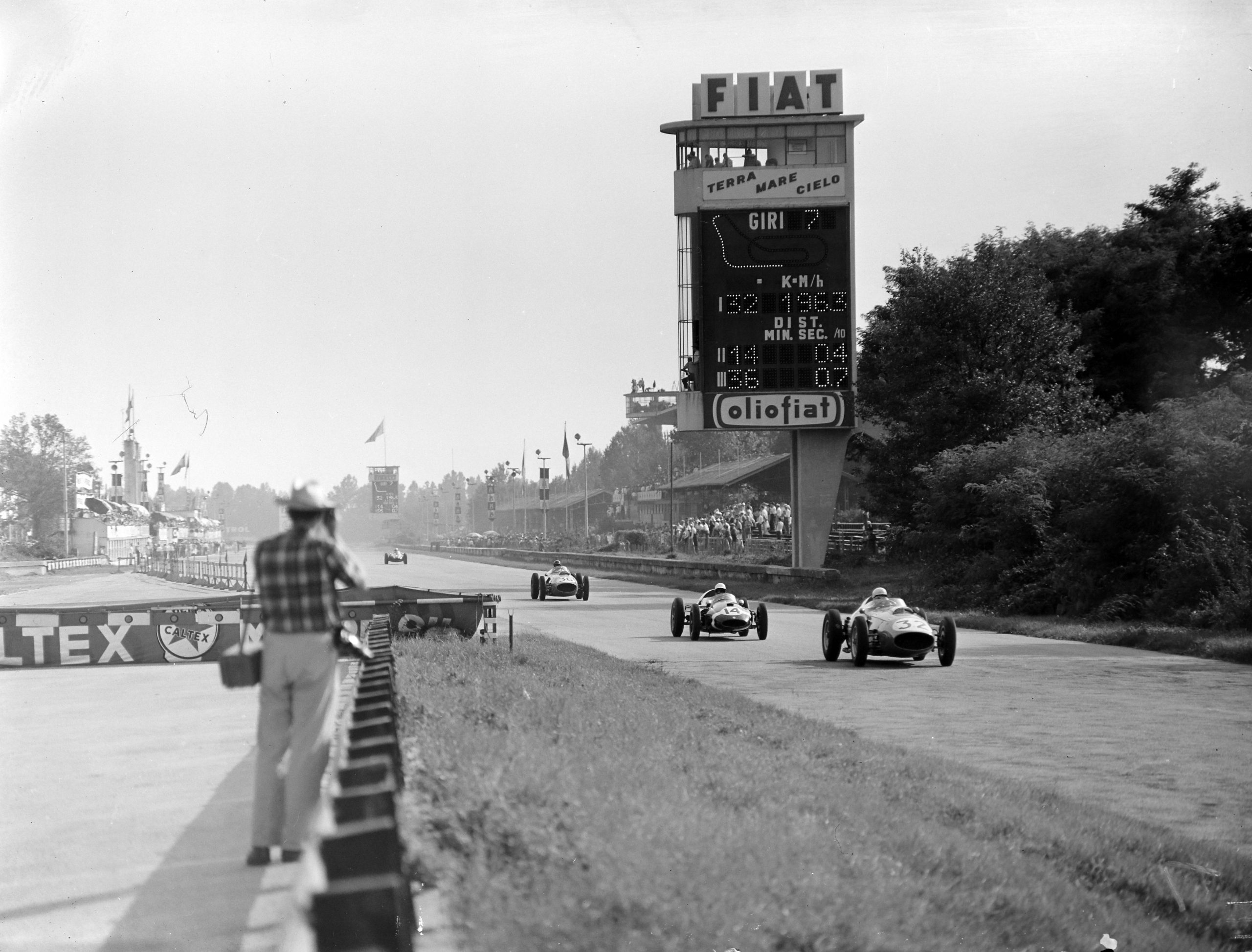 Phil Hill, in a Ferrari 246, leads Stirling Moss driving a Cooper T51 Climax and Dan Gurney also in a Ferrari 246