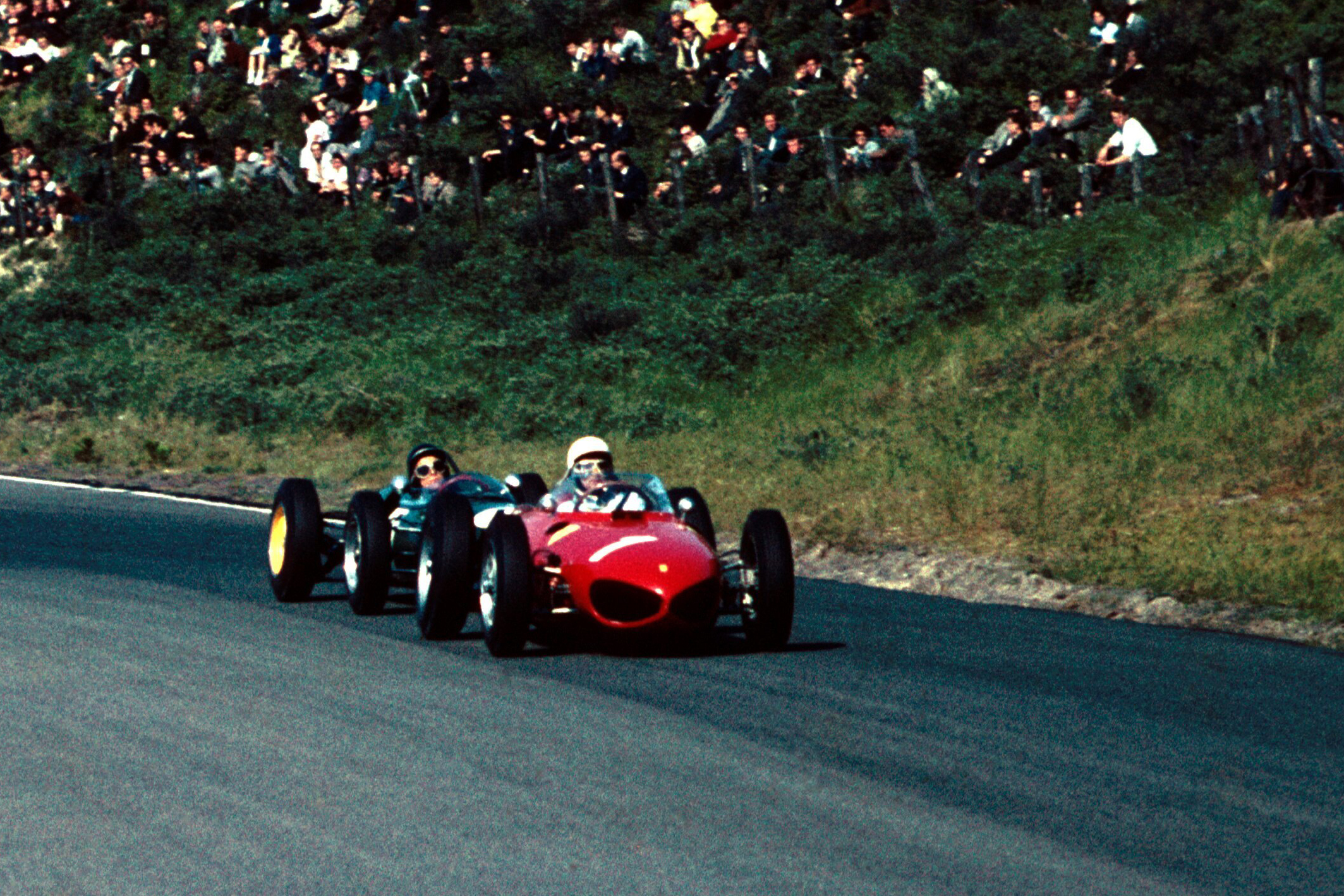 Jim Clark at the wheel of a Lotus 21 chasing Phil Hill in his Ferrari 156.