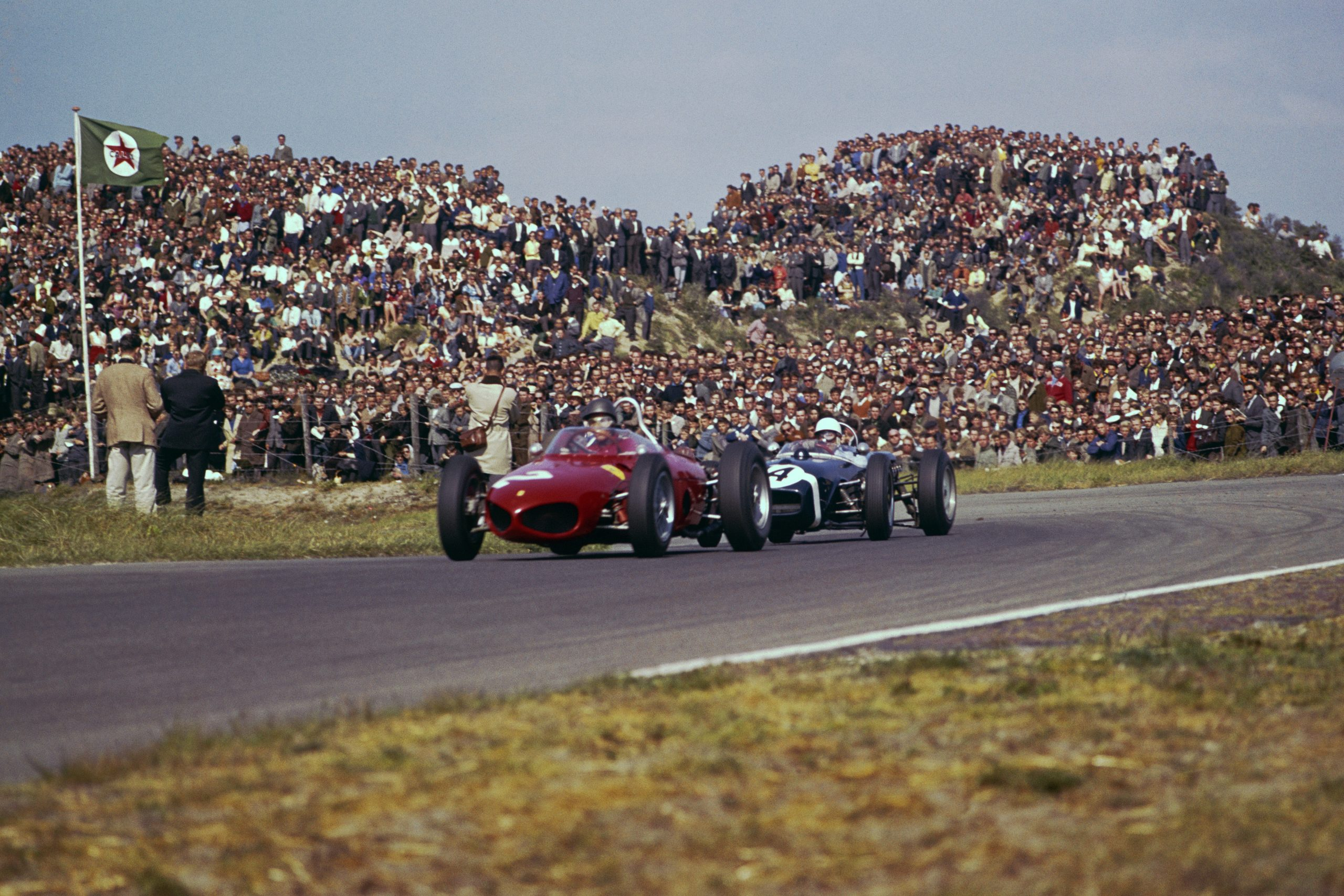 Richie Ginther in a Ferrari Dino 156) leads Stirling Moss in his Lotus 18-Climax.