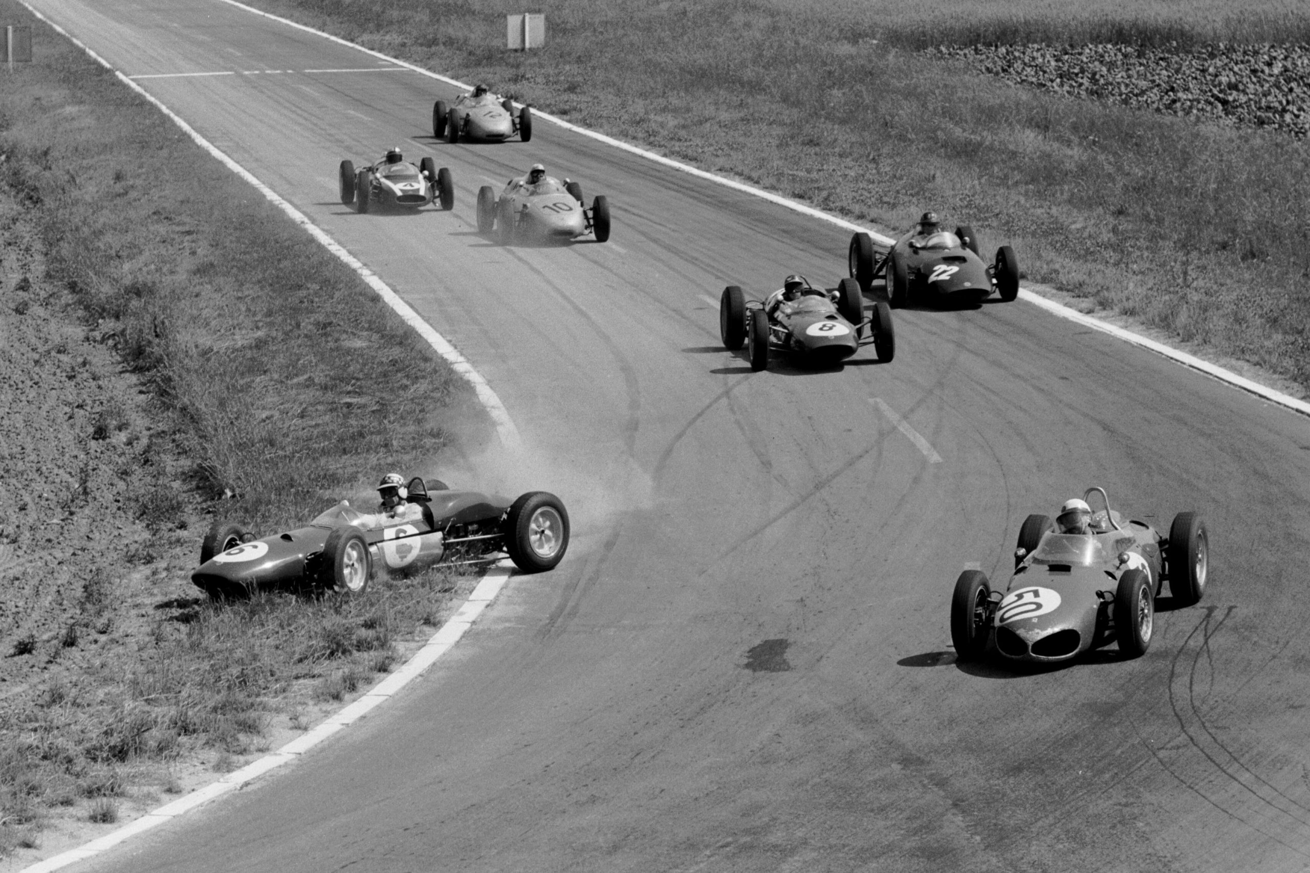 Winner Giancarlo Baghetti leads in the Ferrari 156, while Lotus 21 driver Innes Ireland gets it crossed up.