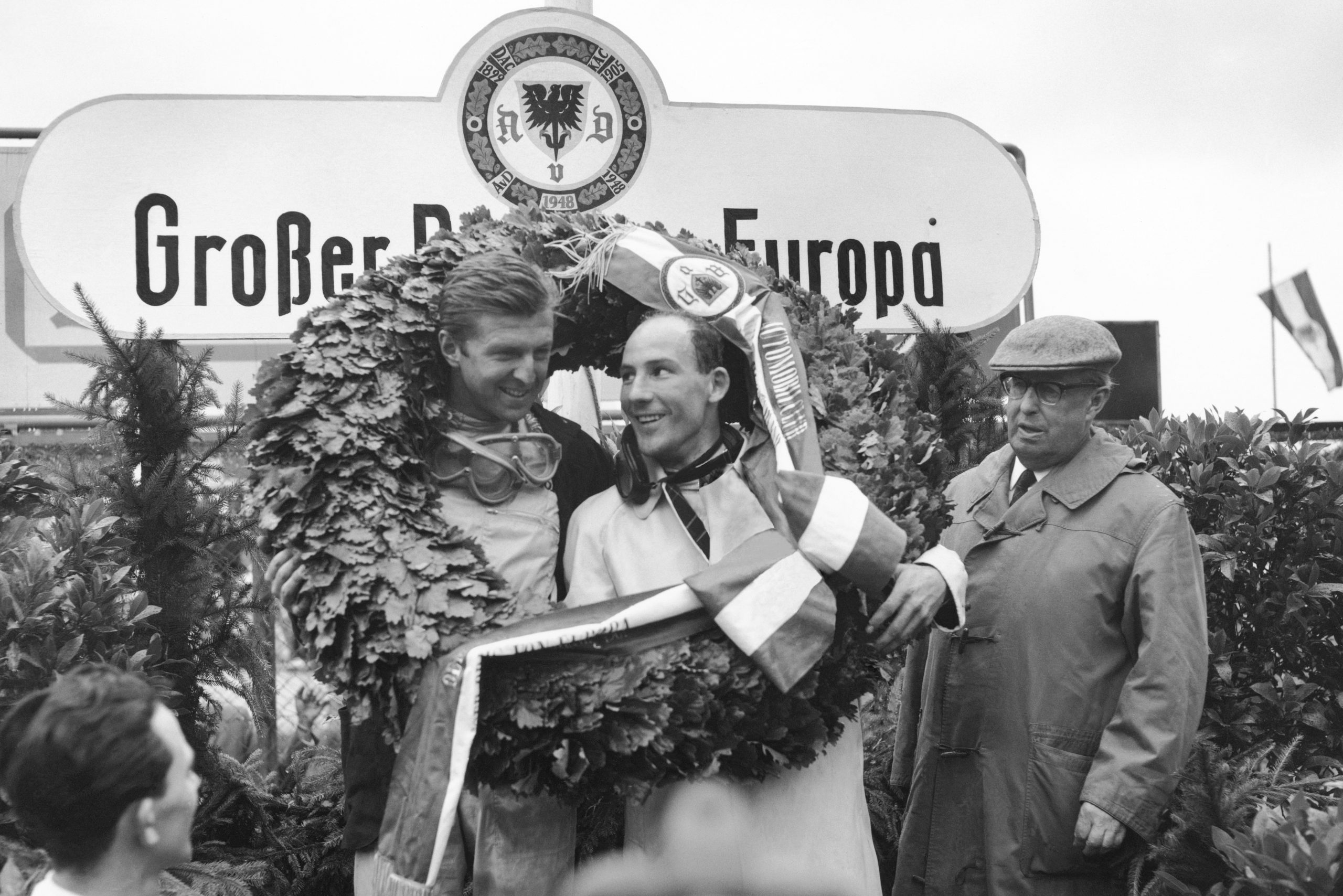 Wolfgang von Trips (Ferrari Dino 156) and Stirling Moss (Lotus 18/21-Climax) celebrate on the podium.