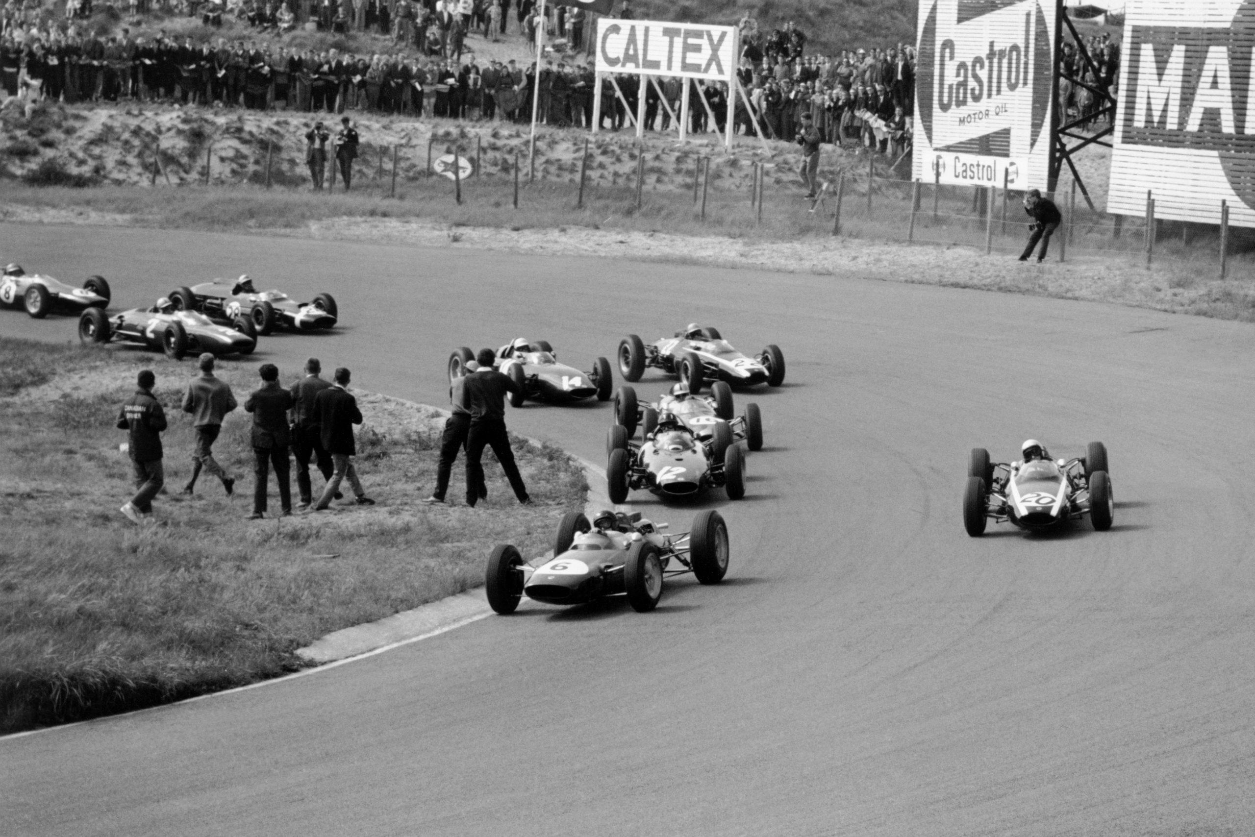 Jim Clark (#6 Lotus 25-Climax) leads Bruce McLaren (#20 Cooper T66-Climax), Graham Hill (#12 BRM P57), Jack Brabham (#16 Brabham BT7-Climax), Tony Maggs (#22 Cooper T66-Climax), Richie Ginther (#14 BRM P57), John Surtees (#2 Ferrari 156), Jo Bonnier (#28 Cooper T60-Climax) and Trevor Taylor (#8 Lotus 25-Climax) into Tarzan Corner at the start.