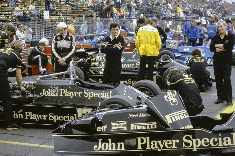 Nigel Mansell, half-wearing a balaclava, looks over at mechanics working on his Lotus 92 Ford.