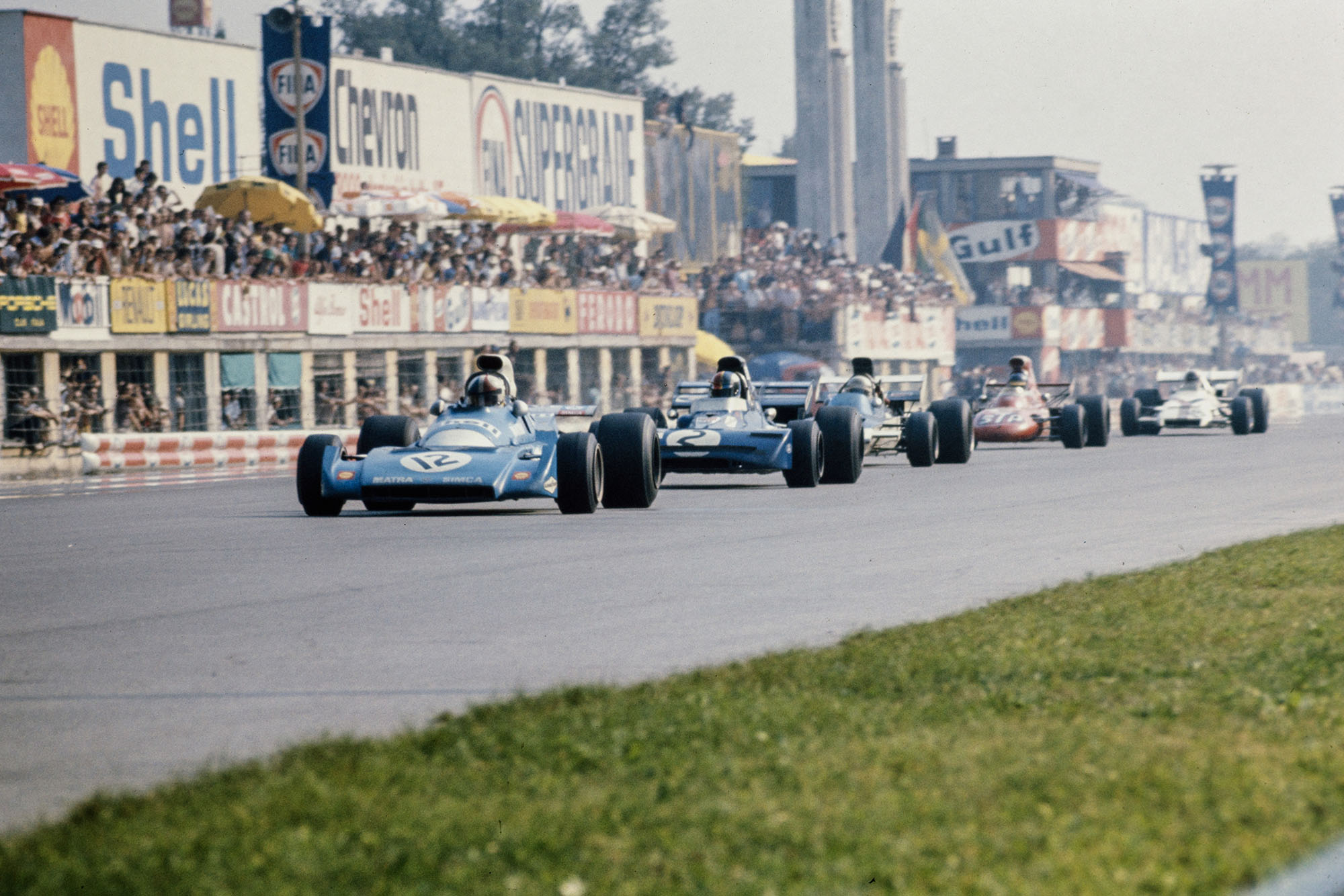 Chris Amon's Matra leads the field down the pit straight.