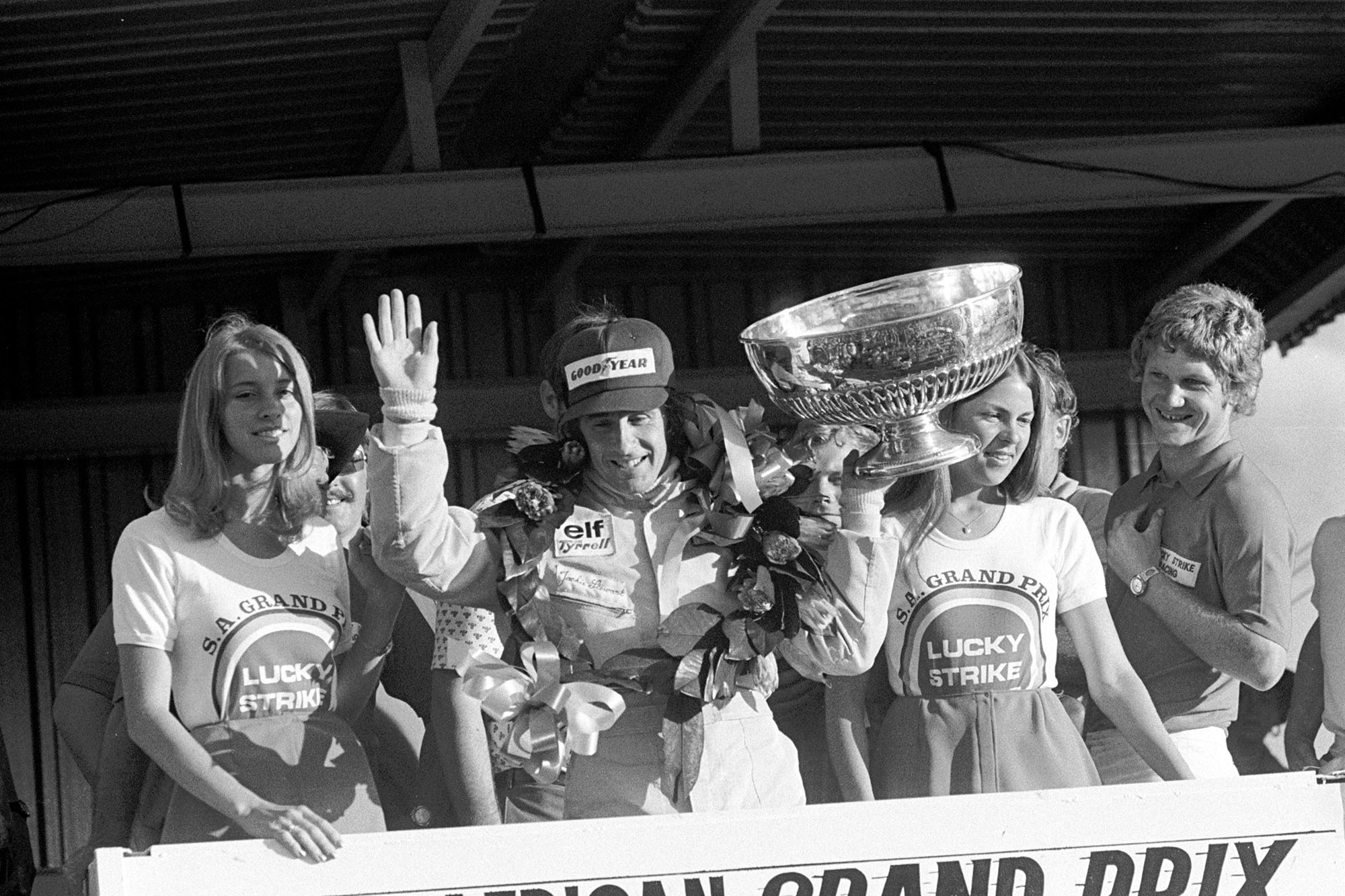 Jackie Stewart waves to the crowd from the podium after winning the 1973 South African Grand Prix for Tyrrell.