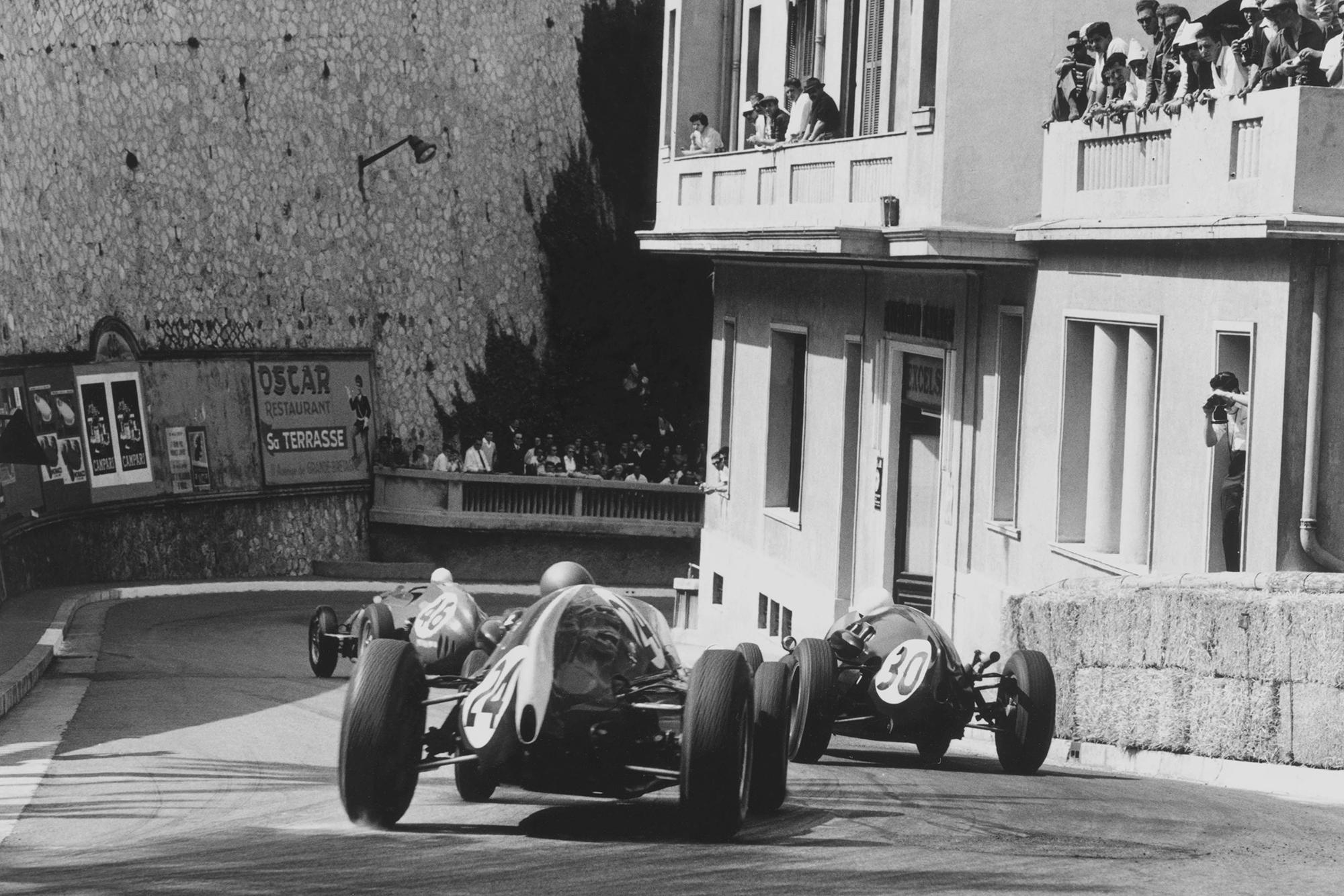 Jean Behra in a Ferrari Dino 246 leads Stirling Moss in his Cooper T51-Climax